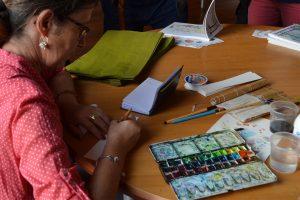 """Dédicace de """"Pau, autour de l'aquarelle"""", Cécile Van Espen de profil peint à l'aquarelle sur un marque page. En premier plan, la palette d'aquarelles"""