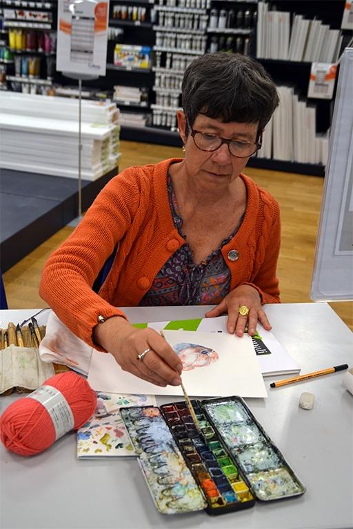 Cécile Van Espen peint une pelote de laine. Elle est de face, image en format portrait. En premier plan, la palette d'aquarelles, puis sur la gauche, une pelote de laine couleur corail. A la suite, la feuille de papier, puis l'aquarelliste. Avec sa main, elle tient le pinceau à réserve d'eau qui prend une couleur dans la palette