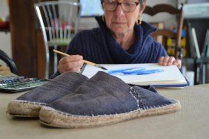 photo : en premier plan une paire d'espadrille couleur bleu et usagée. à la suite l'aquarelliste dont le bloc de papier est posé entre elle et la paire d'espadrille. Elle est entrain de peindre.
