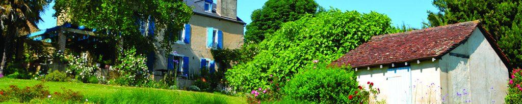 le domaine vignau, maison de maître, aux volets bleu, dans la végétation