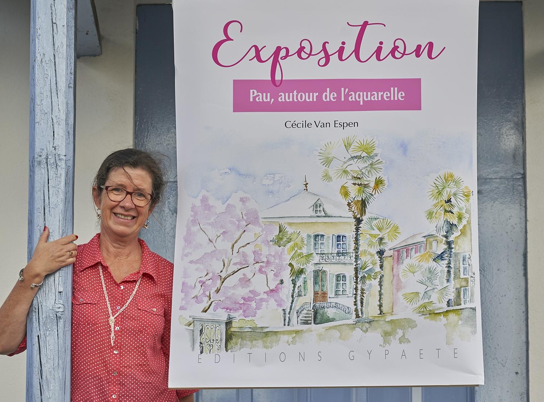 """Cécile Van Espen, aquarelliste, à côté de l'affiche de l'exposition """"Pau, autour de l'aquarelle"""" chez les éditions Gypaète à Pau."""
