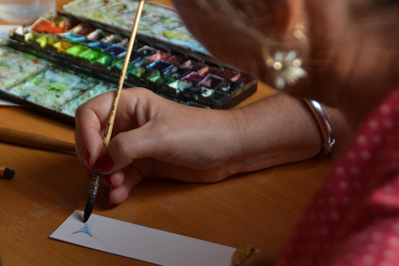 Gros plan sur une main qui tient un fin pinceau à réservoir d'eau.  Ma main dessine une palme sur un marque page. en arrière plan, ma palette