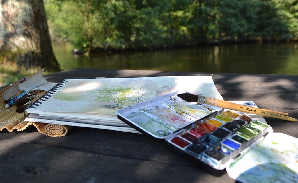 photographie, sur une table de bois, gros plan sur le matériel d'aquarelliste posé l'un sur l'autre, dessus un pinceau à réserve d'eau, dessous une boite de godets usagée, dessous un carnet de papier, dessous une trousse