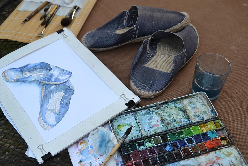 une paire d'espadrilles couleur en jean, devant la même paire en cours de peinture à l'aquarelle. A côté, en premier plan, la palette de peintures, un pinceau. En arrière plan, la trousse de pinceaux
