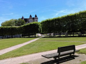 Parc du château de Pau qui est en fond d'image/ en premier plan, les allées du jardin à la française avec un banc sur la droite. Devant le chateau, au pied, une haie d'arbres taillés en rideau.