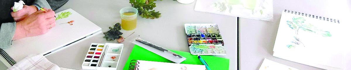 en bandeau, de gauche à droite, une main tiend un pinceau est peint sur une feuille de papier. suit une petite boite de godets d'aquarelles puis divers matériel de peinture
