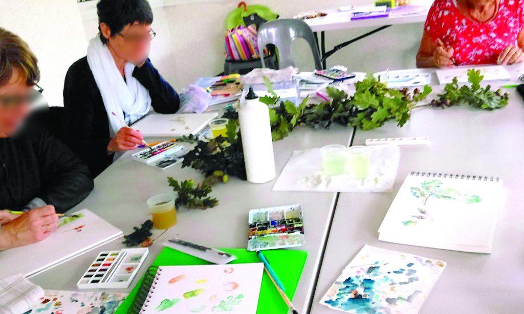 Photo d'un atelier d'aquarelle en salle. Trois personnes autour d'une table, au centre des branches de feuilles de chêne