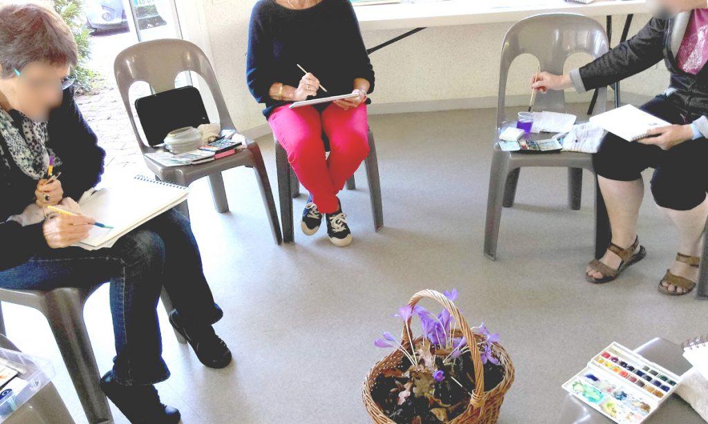 Atelier en salle, à Lescar, des aquarellistes face à leur modèle, un papier de colchique posé au sol et en premier plan à côté d'une palette de godets sur la droite